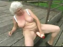 Busty old woman dildoes herself and eats a dick outside