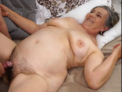 Granny knows how to satisfy her young lover by sucking his huge cock and then spreading her legs for him