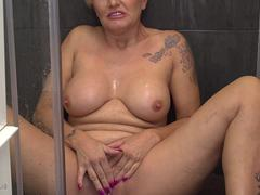 A blonde busty mature tramp is teasing naked in a shower and touching her self on a webcam