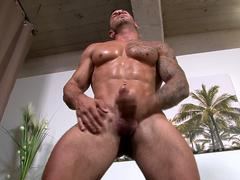 Inked army stud strokes cock on his back